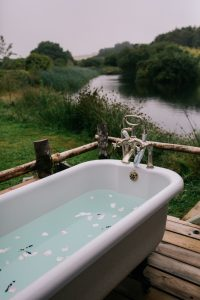 Romantic outdoor bath tub by a wild swimming lake at Pengelly Retreat, Cornwall